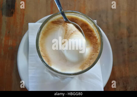 Flat lay view of teaspoon with cream in latte glass drink. Food and drinks background. copy space - Stock Photo