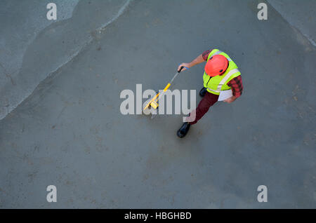 Aerial view of a foreman builder measuring concrete floor with a rolling tape measure in a construction site. Copy - Stock Photo