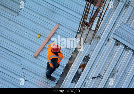 Aerial view of unrecognized civil engineers inspecting the work progress in a construction site. Building development - Stock Photo