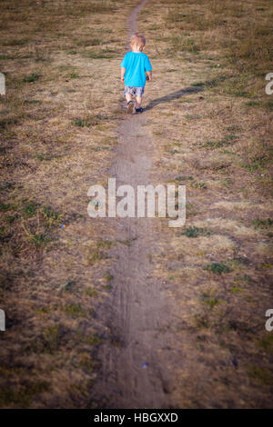 Little boy on a lonely walk - Stock Photo