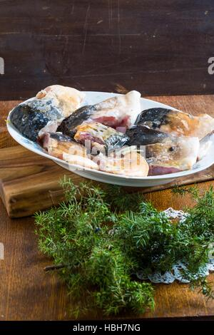 Pieces of carp fish in marinade with oil - Stock Photo