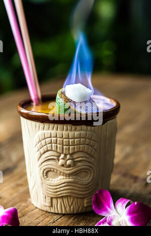 Tiki cocktail for two, in a Tiki mug with a flaming lime as garnish and two straws - Stock Photo