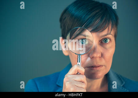 Beautiful businesswoman looking through magnifying glass - search, discover, explore, investigate and analyze concept. - Stock Photo