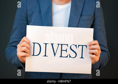 Divestment concept with businesswoman in suite - finance and economics business theme. - Stock Photo