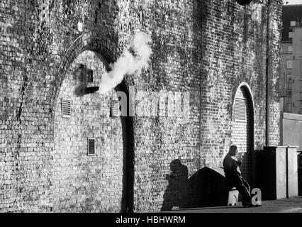 Man sitting smoking underneath the arches, Waterloo, London Borough of Lambeth, Greater London, England, United - Stock Photo