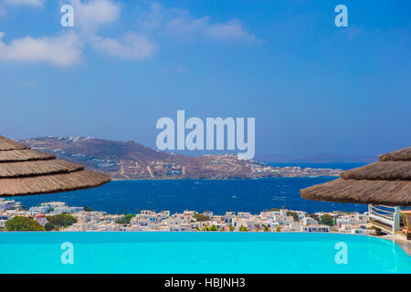 Beautiful view from the edge of infinity pool to the sea and the mountains in the greek town of Mykonos - Stock Photo
