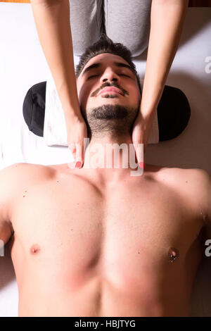 A young masseuse applying a neck massage - Stock Photo