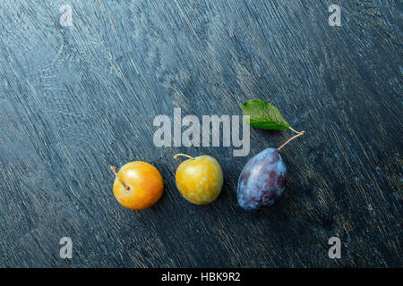 three plums on a black background - Stock Photo