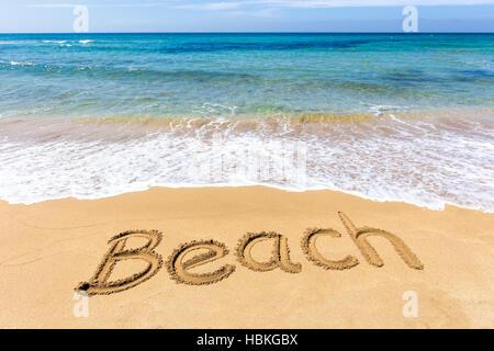 Word Beach written in sand at greek sea - Stock Photo