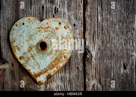 Rusty old trim on keyhole in shape of heart on old wooden door. - Stock Photo