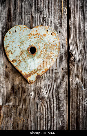 Rusty old trim on keyhole in shape of heart on old wooden door. Vertical shot. - Stock Photo