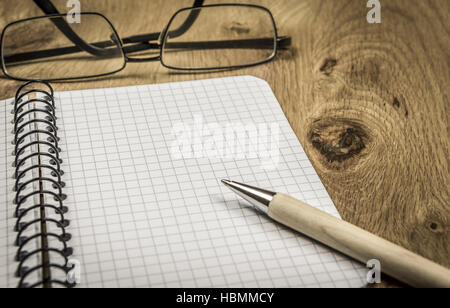 Maths notebook and eyeglasses on wooden desk - Stock Photo