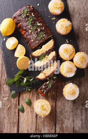 Sliced lemon cake with chocolate and lemon muffins with icing and zest close-up on the table. vertical view from - Stock Photo
