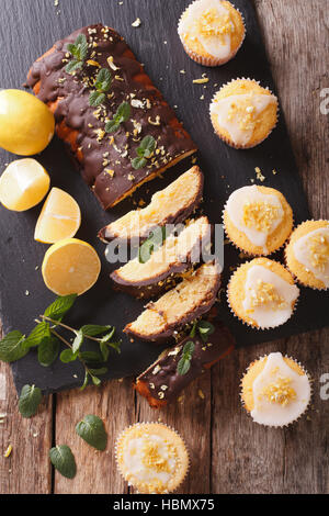 Lemon cake with chocolate and lemon muffins with frosting close-up on the table. vertical view from above - Stock Photo