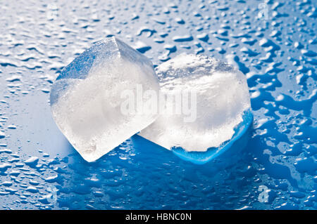 two ice cubes on a wet surface - Stock Photo