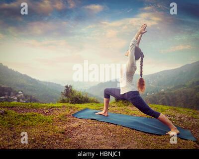 Woman doing yoga asana Virabhadrasana 1 - Warrior pose outdoors - Stock Photo