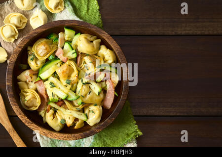 Baked cheese tortellini or belly button pasta with zucchini, bacon and thyme in wooden bowl, photographed overhead - Stock Photo