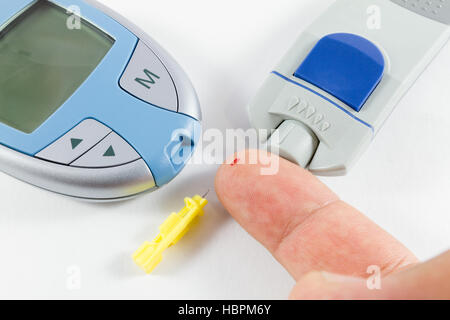 Close-up of glucometer and patient's finger with blood drop on white background. Yellow needle also visible - Stock Photo