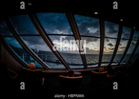 Hurtigruten passenger ship MS Polarlys Explorer lounge on deck 7 at the front of the ship, cruising into the sunset, - Stock Photo