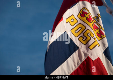 Norwegian national flag with Post insert flying from the stern of Hurtigruten MS Polarlys, Norway. - Stock Photo
