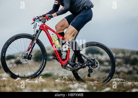 closeup of athlete mountainbiker and sport bicycle racing in water bottle during Crimean race mountainbike - Stock Photo