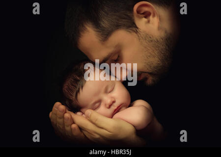 Little 15 days old baby lying securely on his Dad's arms, against a black background