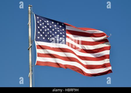 National Flag of the United States of America flying high in the sky at Sunset Beach, in Florida. - Stock Photo