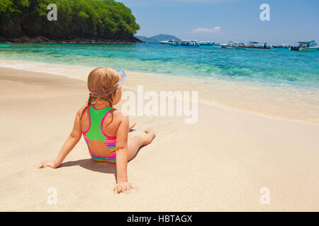 Beautiful little snorkeler relax on sunny white sand ocean beach. Happy baby have fun, look at surf in tropic blue - Stock Photo