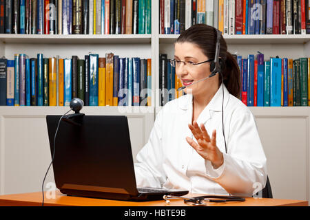 Doctor sitting with a headset or headphone at her desk in front of a computer with an attached camera and talking with a patient
