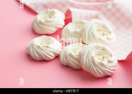 Sweet white meringue on pink background. - Stock Photo