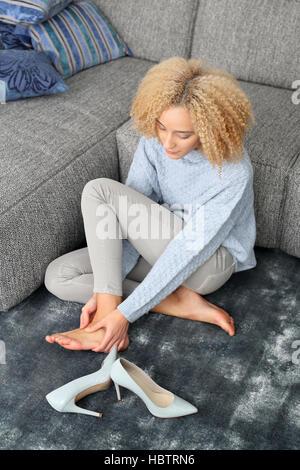 Foot massage. Aching feet. Woman massaging tired, aching feet. - Stock Photo