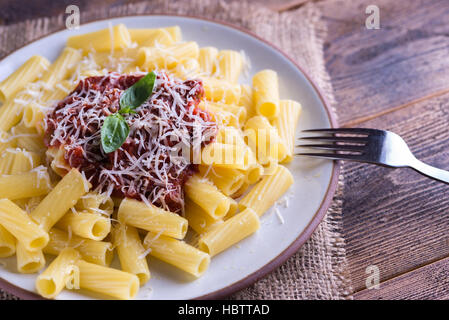 Pasta with tomato sauce and parmigiano on natural wooden table with fork. - Stock Photo