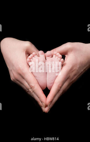 A closeup crop of a mother's hands in a loveheart shape holding her tiny newborn baby's feet against a black background - Stock Photo
