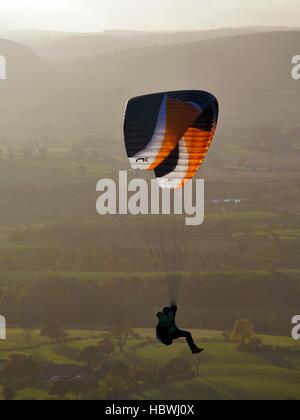 man flying paraglider at sunset - Stock Photo