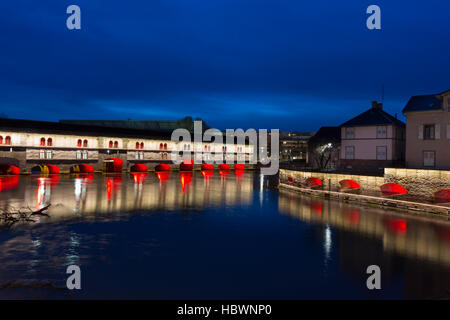 illumined Ponts Couverts and Barrage Vauban at twilight reflected in the waters on the River Ill, Alsace France