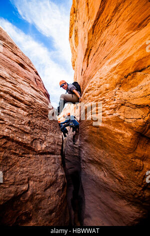 A group of young men working through Raven, a slot canyon in the Escalante, Utah - Stock Photo