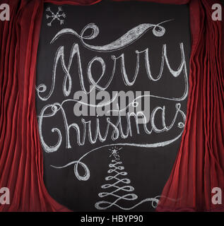 Merry Christmas hand drawn lettering with chalk on blackboard framed by red curtains. Elegant unique design with - Stock Photo
