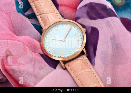 Pink wrist watch on colourful silk fabric background - Stock Photo