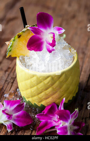 Tiki cocktail served in a pineapple mug with fresh pineapple and orchid flower granish. - Stock Photo