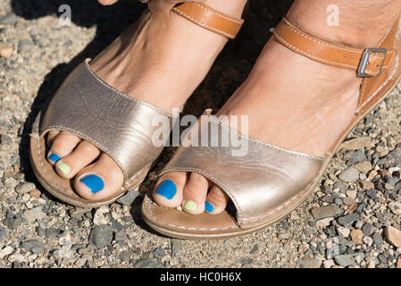 Woman's feet with sandals and painted toenails. - Stock Photo