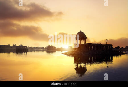 Silhouette of Temple on the Gadi Sagar lake at yellow sunset sky in Jaisalmer, Rajasthan, India - Stock Photo