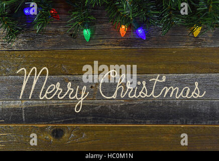 Merry Christmas in rope design with glowing Christmas lights on rustic barn wood - Stock Photo