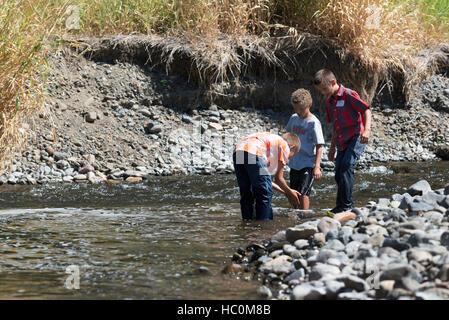 Kids exploring a river in Northeast Oregon. - Stock Photo