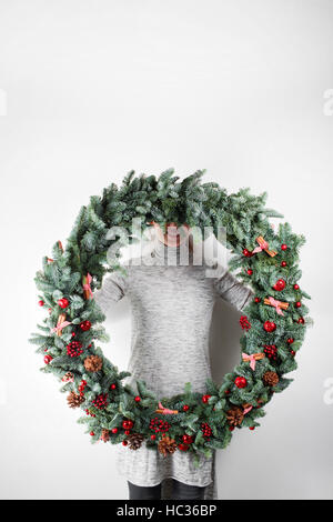 young woman holding christmas large wreath in hands in light, seasonal holidays, rustic theme, adorning - Stock Photo