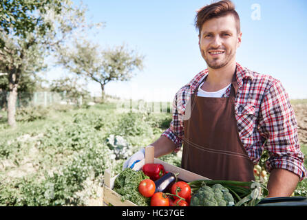 Man is standing with crate full of vegetables - Stock Photo