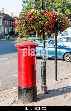 England, Tenterden. Traditional British red letter box, also known as pillar box, with two flower baskets hanging - Stock Photo