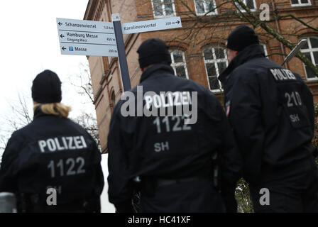Police officers pictured at an entrance in the security area around the exhibition halls in Hamburg, Germany, 7December - Stock Photo