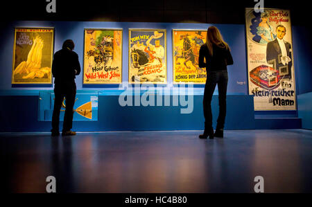 Stuttgart, Germany. 08th Dec, 2016. Visitors look at old film posters at the exhibition 'Carl Laemmle presents. - Stock Photo