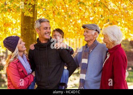 Happy multi-generation family standing at park - Stock Photo