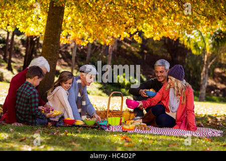 Happy family having breakfast at park - Stock Photo